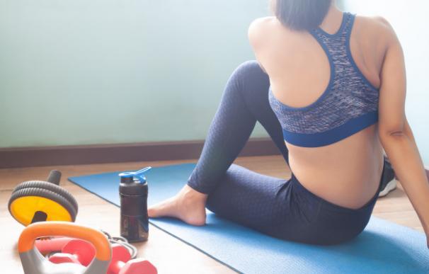 Una mujer realiza ejercicio junto a un batido