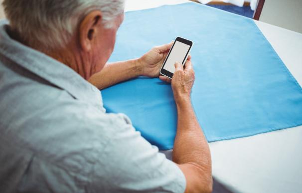 Fotografía de un jubilado con un móvil.