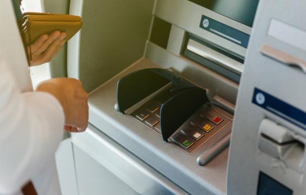 Fotografía de un persona sacando dinero del cajero. Algunos bancos en España permiten cobrar la pensión antes a los jubilados por le coronavirus.
