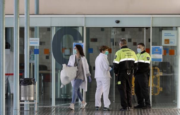 Dos agentes de seguridad junto a dos enfermeras en la entrada principal del Hospital del Mar de Barcelona.