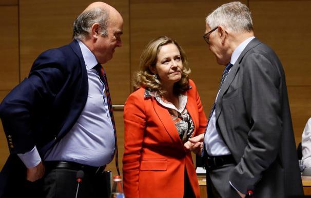 La ministra de Economía, Nadia Calviño (c), conversa con el vicepresidente del Banco Central Europeo, Luis de Guindos (i), y el director gerente del Mecanismo Europeo de Estabilidad, Klaus Regling (d), antes del comienzo del Consejo de Ministros