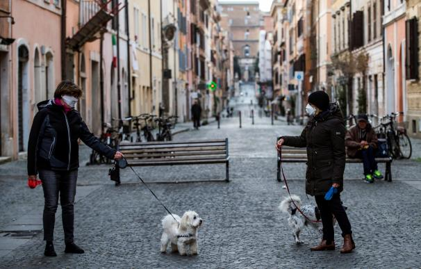 Fotografía de dos personas paseando al perro en Roma durante la crisis del coronavirus.