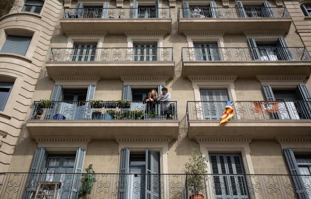 Dos personas se asoman al balcón durante el tercer día laborable del estado de alarma por coronavirus, en Barcelona/Catalunya (España) a 18 de marzo de 2020.