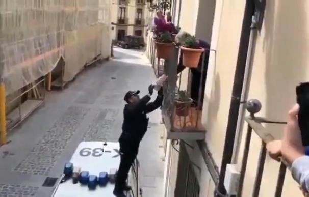 El agente sobre el coche patrulla para hacer la entrega. /L.I.