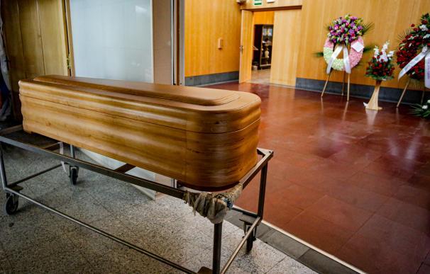 Un ataúd junto a varias coronas de flores fúnebres en el Tanatorio Crematorio Mémora Coslada