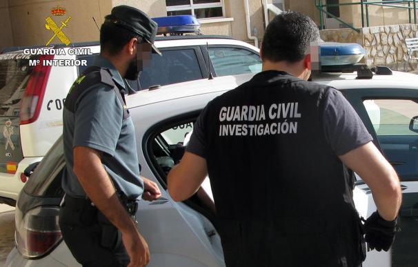 Los agentes de la Guardia Civil, durante el traslado de uno de los detenidos