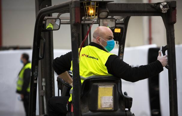 Un empleado carga mascarillas para un transporte