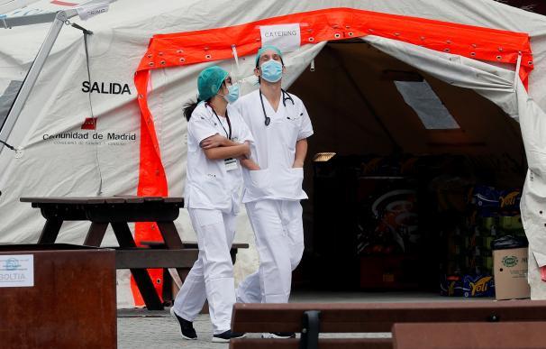 Personal sanitario descansa en los exteriores del Hospital de Ifema, en Madrid.