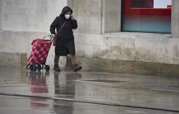 Una mujer con mascarilla camina bajo la lluvia con el carro de la compra durante el Martes Santo y la cuarta semana del estado de alarma decretado por el Gobierno por la crisis del coronavirus, en Pamplona/Navarra (España) a 7 de abril de 2020.