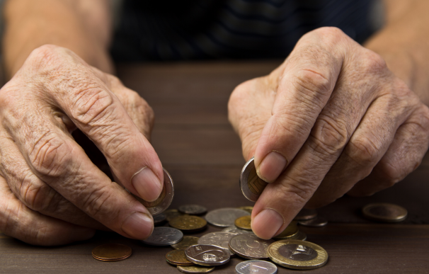 Fotografía de un jubilado contando dinero. Si rescatan un plan de pensiones pueden tener que pagar el irpf.