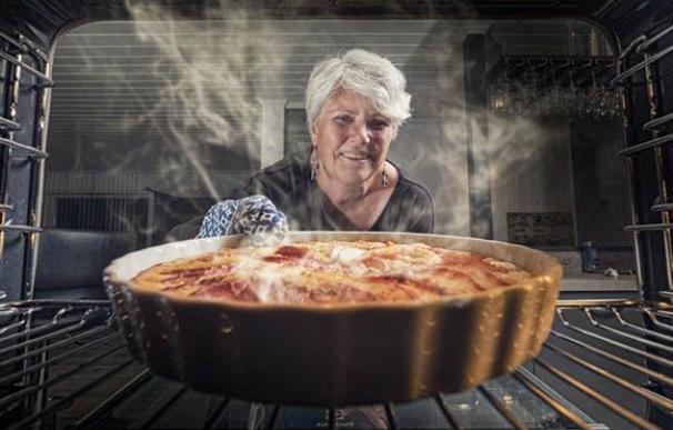 Una mujer retira del horno una tarta de manzana