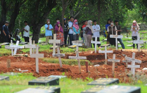 Personas con mascarilla por el coronavirus en un cementerio de Yakarta (Indonesia)