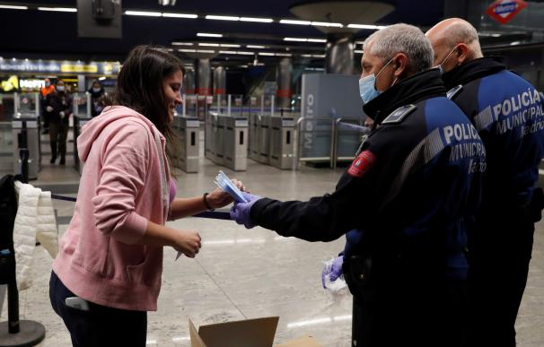 Policías entregan una mascarilla a una mujer en la estación de metro de Nuevos Ministerios en Madrid, este lunes. Según anunció el pasado sábado el ministro de Sanidad, Salvador Illa, las fuerzas de seguridad repartirán 10 millones de mascarillas este lun