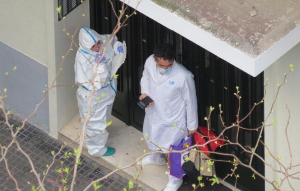 Dos sanitarios en un portal visitan a un enfermo de coronavirus