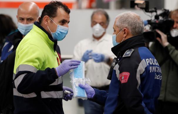 Policías entregan mascarillas en la estación de metro de Nuevos Ministerios en Madrid, este lunes. Según anunció el pasado sábado el ministro de Sanidad, Salvador Illa, las fuerzas de seguridad repartirán 10 millones de mascarillas este lunes a los trabaj