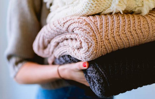 Una joven recoge la ropa recién lavada y planchada