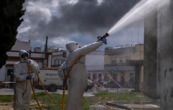 Miembros del Infoca realizan labores de desinfección en el Centro de Salud de San Juan del Puerto (Huelva). /EFE/Julián Pérez