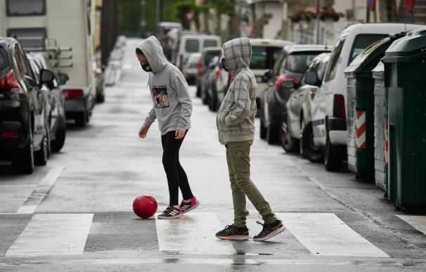 niño en la calle jugando a la pelota coronavirus