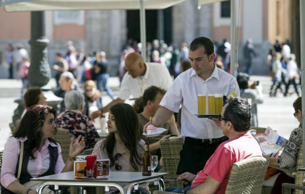 Un camarero sirve bebidas en una terraza en la plaza de la Virgen de Valencia. (EFE)