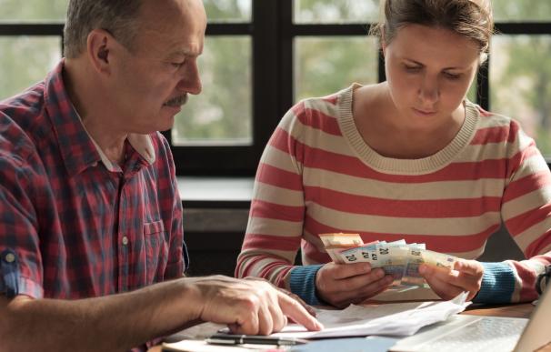 Fotografía de una pareja contando el dinero de un subsidio por desempleo.