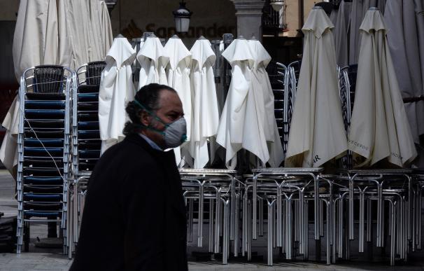 Un hombre ataviado con una mascarilla pasa por delante de una terraza recogida de un bar, este miércoles en el centro de Valladolid durante el cuadragésimo sexto día de confinamiento tras decretarse el estado de alarma debido a la pandemia del coronavirus