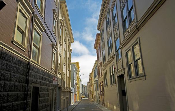 Fotografía de una calle con viviendas. Quienes vendan su casa para comprar otra tienen ventajas en el IRPF.