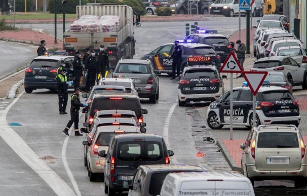 Fotografía de un control de la policía repartiendo mascarillas.