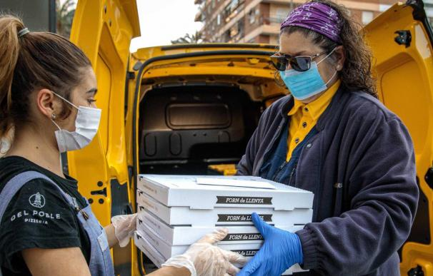 Una empleada le entrega pizzas a una mujer