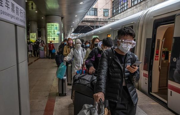 Decenas de pasajeros llegados de Wuhan en una estación de Pekín. / EFE