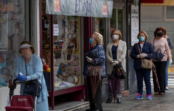 Personas haciendo cola con su mascarilla en Sevilla