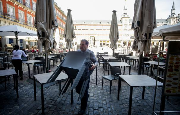 Varios empleados de un bar de la Plaza Mayor de Madrid recogen la terraza un día antes de que se cierre toda la hostelería para frenar contagios por coronavirus, en Madrid