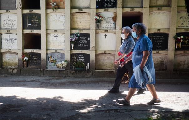 Dos personas protegidas con mascarillas acuden a visitar a sus familiares en el cementerio