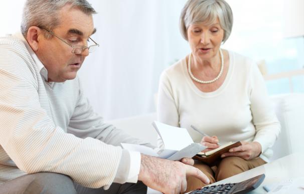 Fotografía de dos trabajadores consultando su plan de pensiones. El cambio o despido de una empresa afecta al plan de pensiones.