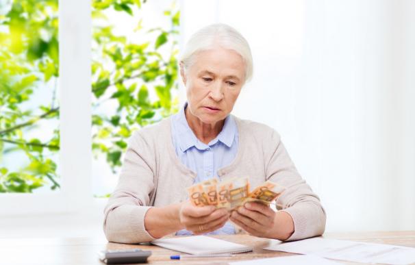 Fotografía de una jubilada contando el dinero de su pensión. Los pensionistas españoles tienen dos pagas extras cada año.