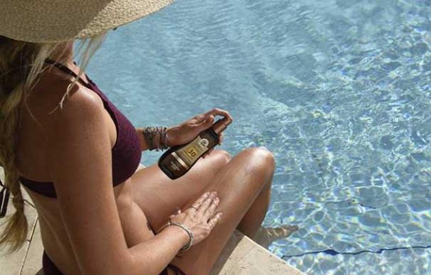 Una joven en una piscina se aplica protección solar sobre la pierna