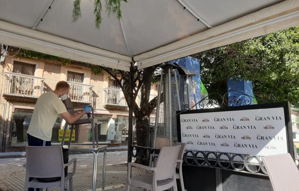 Un camarero limpia el mobiliario de su terraza a pocas horas de abrir el establecimiento