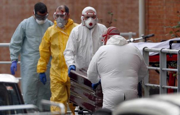 Trabajadores de una funeraria protegidos trasladan de la morgue a un fallecido por coronavirus. EFE/LUIS TEJIDO