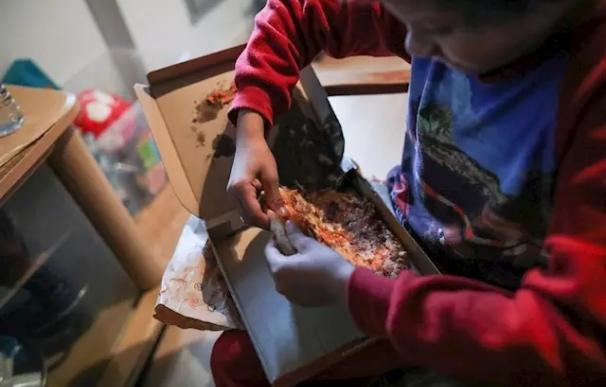 Un niño come un trozo de pizza del menú infantil de Telepizza mientras ve la televisión en su casa. /Jesús Hellín/ Europa Press