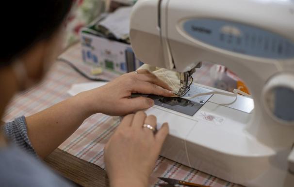 Una mujer fabricando mascarillas