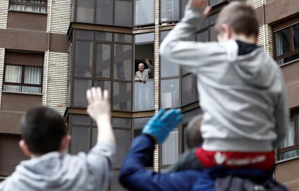 Dos niños saludan a su abuelo desde la ventana