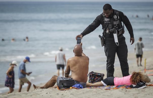 Un policía reclama información a un usuario en una playa de Florida.