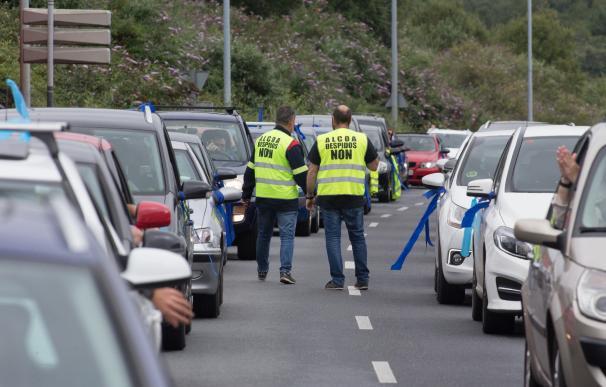 Dos trabajadores de Alcoa caminan entre los coches durante una marcha de coches en caravana convocada por el comité de Alcoa San Cibrao