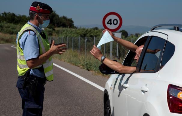 Un conductor enseña la documentación a un mosso en un control en la zona confinada de Lleida.