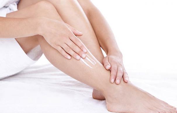 Una mujer se aplica crema hidratante en las piernas