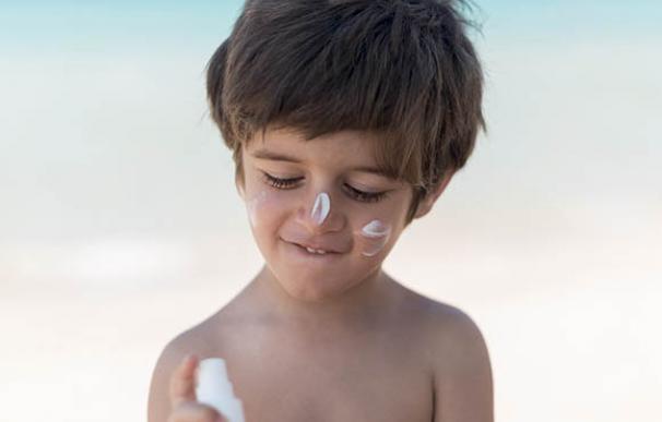 Un niño se aplica crema solar en la cara