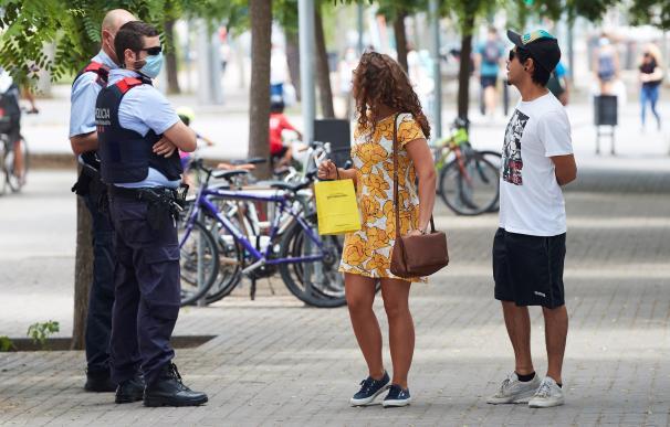 Unos agentes de los Mossos d'Esquadra informan a una pareja del uso obligatorio de la mascarilla, este viernes en Barcelona.