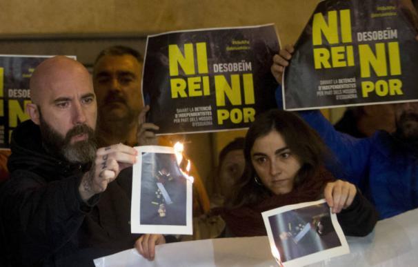 El concejal de la CUP en el Ayuntamiento de Barcelona Josep Garganté (i) quema una foto del Rey