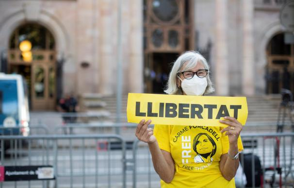 Una mujer muestra una pancarta de apoyo a los miembros de la Mesa del Parlament de la pasada legislatura