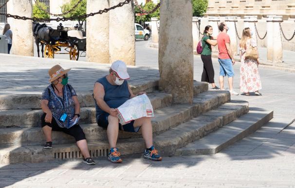 Dos turistas buscan la sombra en pleno centro de Sevilla durante este verano.