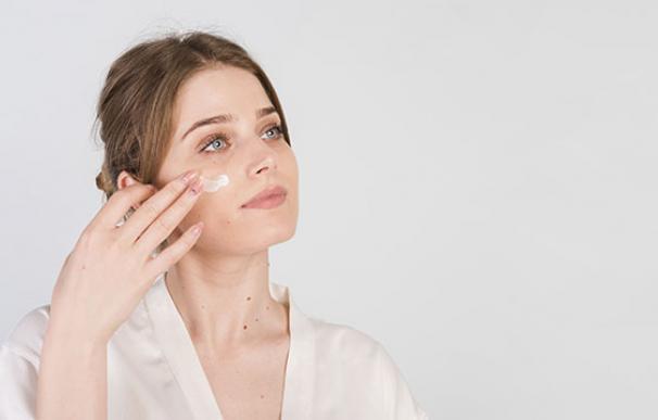 Una joven se aplica crema en la cara